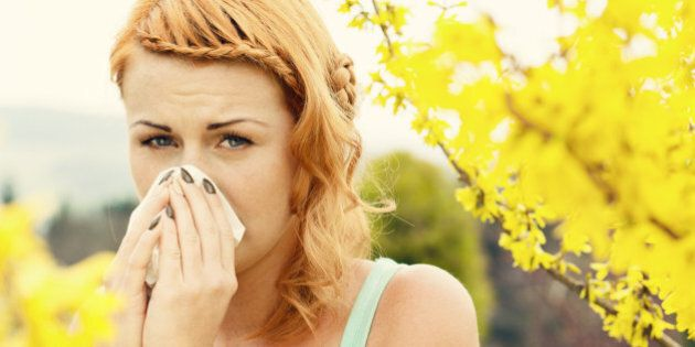 Young woman sneezing among flowers
