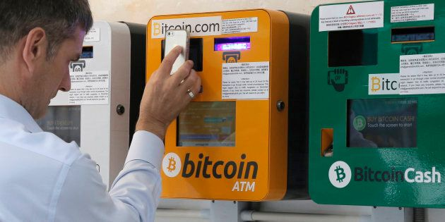 A man uses a bitcoin ATM in Hong Kong, Fri. May 11, 2018. Demand for bitcoin could single-handedly derail efforts to limit global warming, scientists said on Monday.