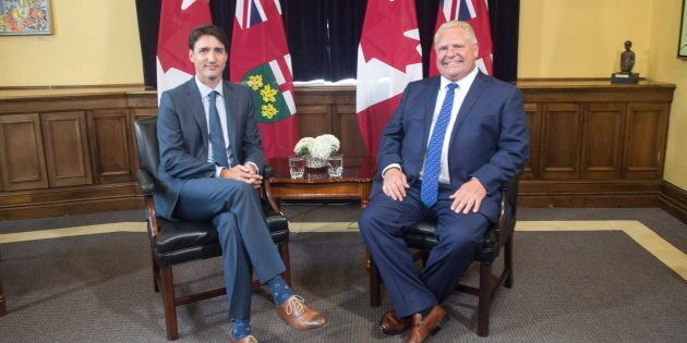Prime Minister Justin Trudeau sits with Ontario Premier Doug Ford at the Ontario Legislature in Toronto...