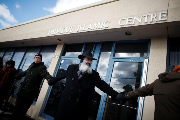 """People from the Holy Blossom Temple Synagogue and the Fairlawn United Church form a """"Ring of Peace"""" outside The Imdadul Islamic Centre, during prayers, to show solidarity in condemning the deadly shooting at the Quebec Islamic Cultural Centre, in Toronto on Feb. 3, 2017."""