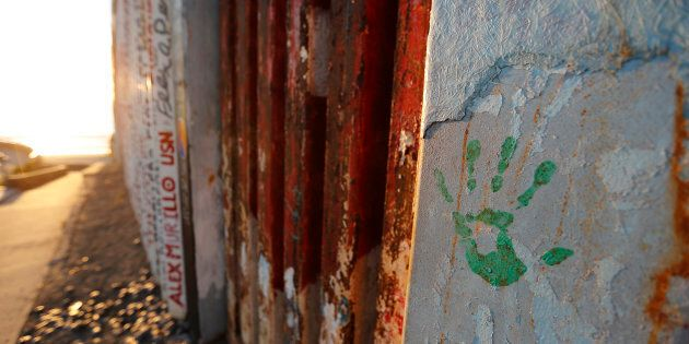 A hand print in honor of migrants that have been killed or are missing is seen on a border wall structure...