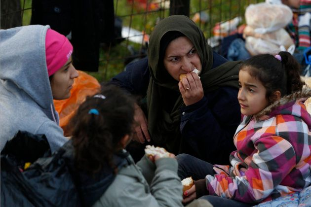 Migrants eat after having camped near a police barricade at a border crossing in Izacici near Bihac,...