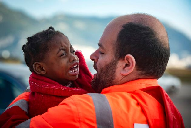 In this photo taken on Saturday, Oct. 27, 2018, a child is carried by a member of Spain's Maritime Rescue...