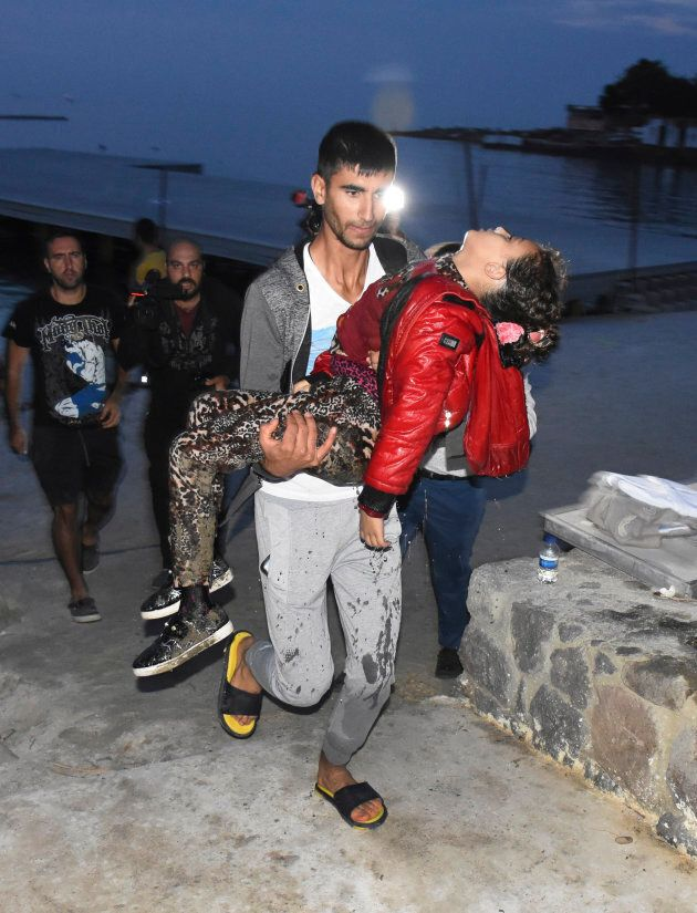 A man carries a dead migrant after a boat carrying migrants sank in the Aegean Sea, near the resort of...