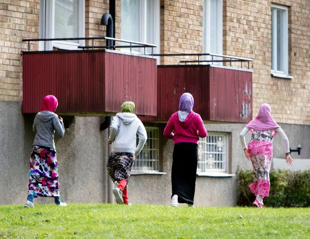 In this Aug. 30, 2018 photo migrant girls from Africa run along their apartment house in Flen, some 100...