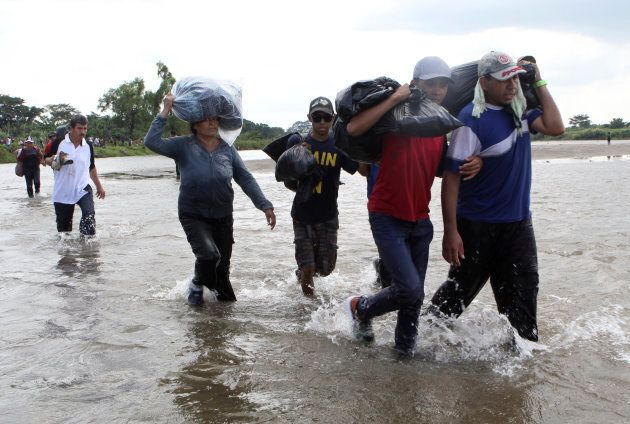 Salvadoran migrants cross the Suchiate river, the border between Guatemala and Mexico, on Friday, Nov....