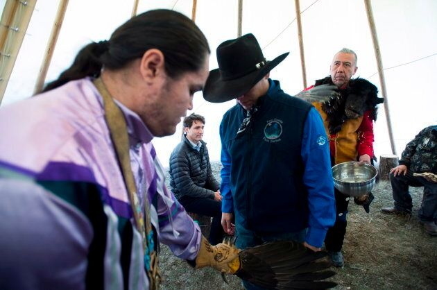Prime Minister Justin Trudeau looks on as a chief receives a water cleansing by spiritual leader Cecil...