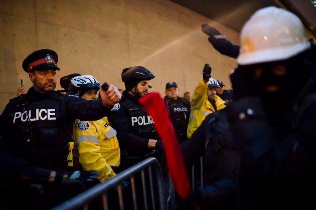 Police pepper spray protesters as they clash prior to a Toronto Munk debate featuring Steve Bannon and...