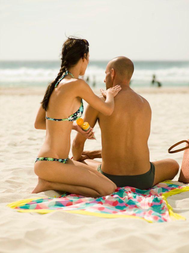 Woman applying suntan lotion on her