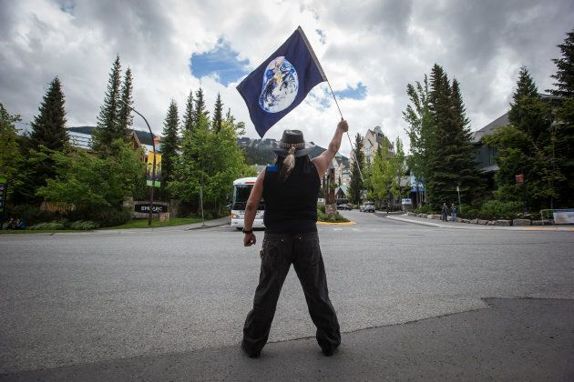 A demonstrator holds a flag with an image of Earth during a protest against the Kinder Morgan Canada...