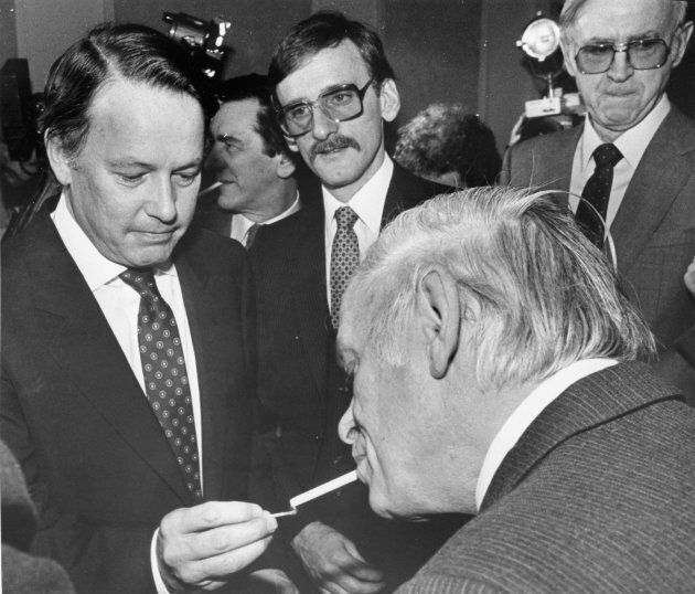 Landry lights a cigarette for Quebec Premier Rene Levesque on Mar. 5, 1984, in Quebec