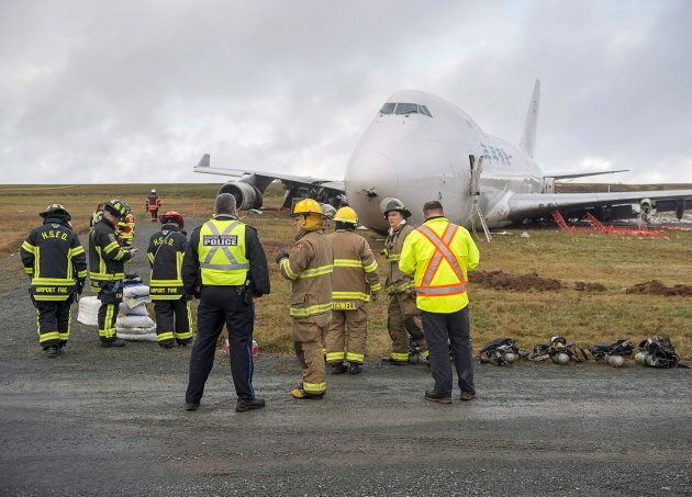 First responders stand near a SkyLease Cargo plane that skidded off a runway at Halifax Stanfield International