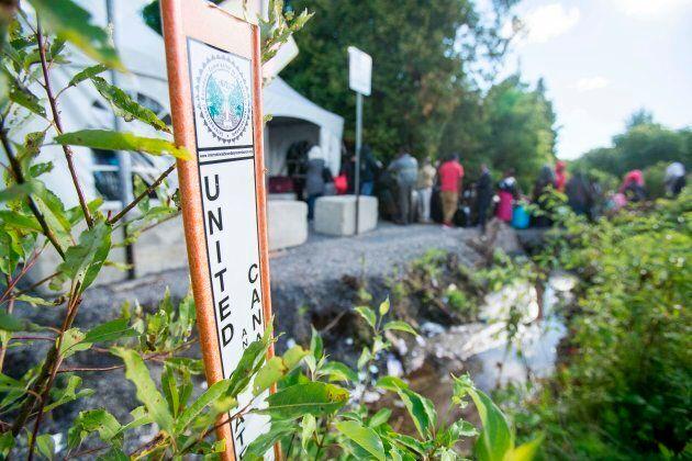 A line of asylum seekers from Haiti wait to cross the Canada/U.S. border near Champlain, NY on Aug. 6,