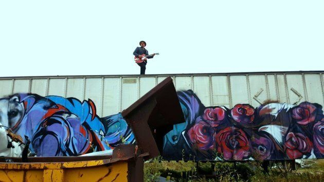 Adrian Sutherland on top of a boxcar during Midnight Shine's music video shoot for