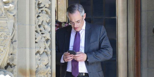 Conservative MP Tony Clement checks his phone on Parliament Hill in Ottawa on May 11,