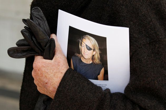 A man holds a sign honouring Sunday Times journalist Marie Colvin, who died in Syria in