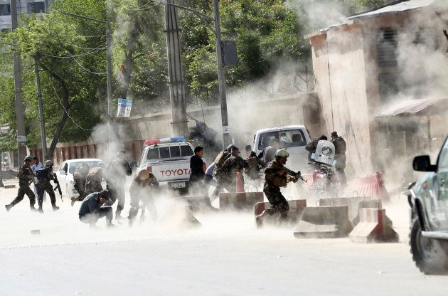 Security forces run from the site of a double suicide attack in Kabul, Afghanistan, on April 30,