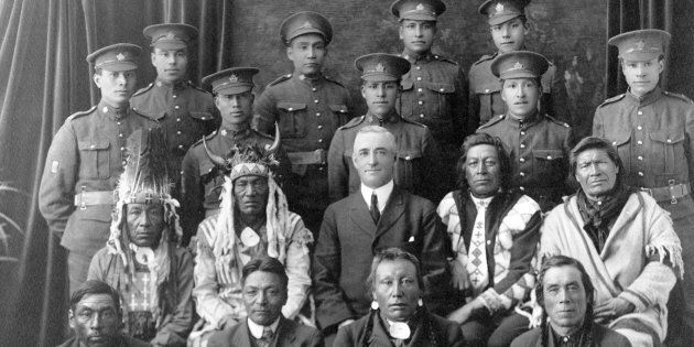 Recruits from File Hills, Sask. pose with elders and a government representative in a 1915 photo from...