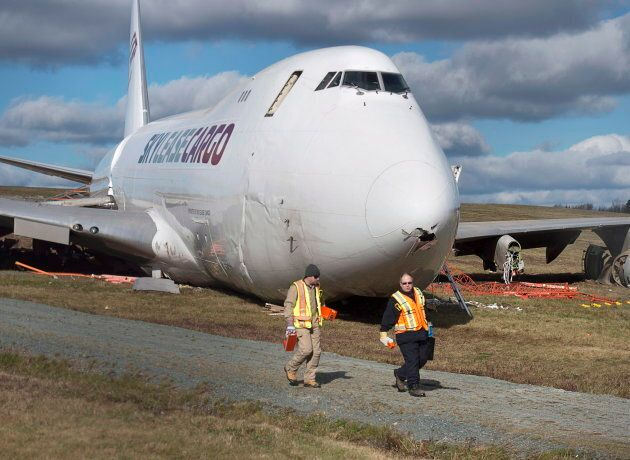 Police officers stand near a SkyLease Cargo plane that skidded off a runway at Halifax Stanfield International...