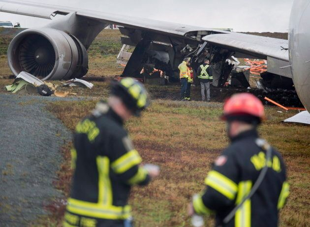 Investigators stand near a SkyLease Cargo plane that skidded off a runway at Halifax Stanfield International...