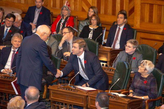 New Brunswick Progressive Conservative MLA Gregory Thompson shakes hands with former Premier Brian Gallant...