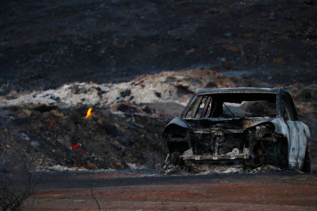 The burnt wreckage of a vehicle is seen along a road as a flames are seen, in the aftermath of the Woolsey...