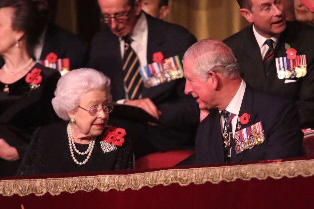 Queen Elizabeth II speaks with Prince Charles.