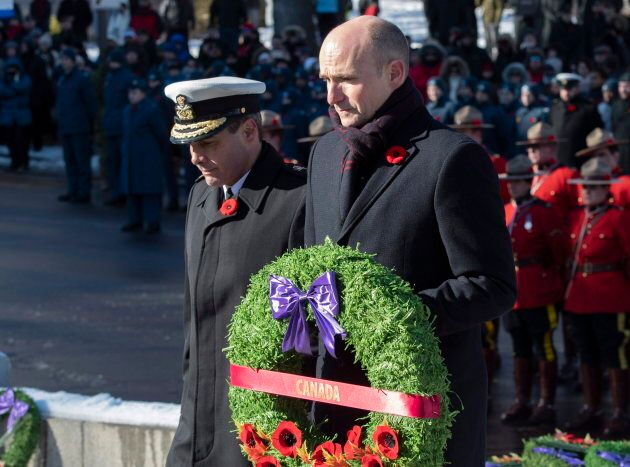 Minister of Families, Children and Social Development Jean-Yves Duclos carries a wreath to the cenotaph...