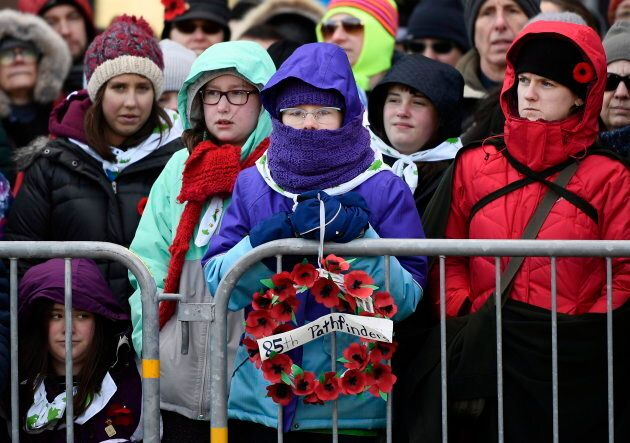 A girl holds a wreath of poppies before the start of Remembrance Day ceremonies at the National War Memorial...