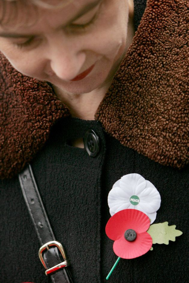 A woman wears a red poppy of remembrance and a white poppy of peace on Armistice Day at the Cenotaph...