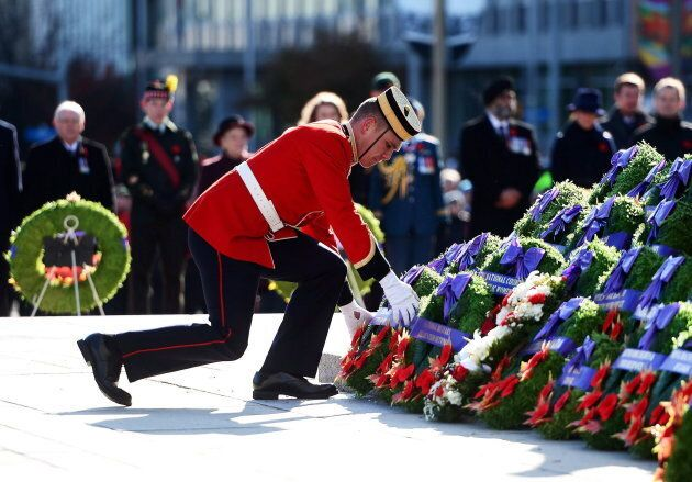 A soldier places a predominantly red wreath during Remembrance Day ceremonies at the National War Memorial...