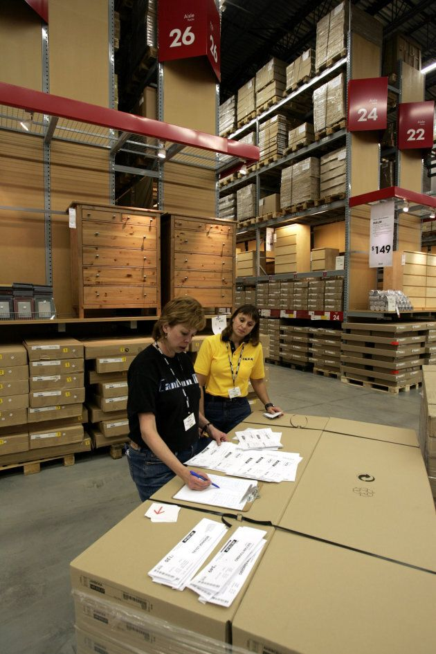 Ikea employees look over labels at the furniture store in Canton Township,