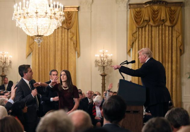 A White House staff member reaches for the microphone held by CNN's Jim Acosta as he questions U.S. President...