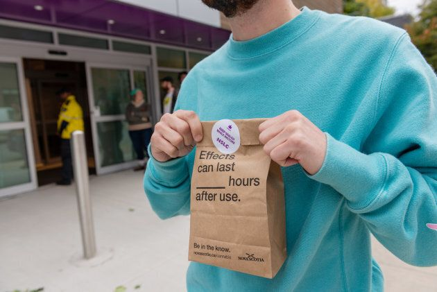 A customer displays a sealed bag containing legally purchased cannabis products outside of a Nova Scotia...