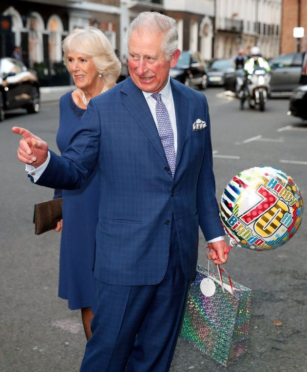 Prince Charles, with his wife Camilla, holds a birthday gift on his 70th birthday at Spencer House in London on Wednesday.