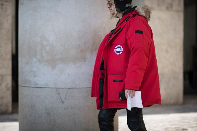 A guest is seen wearing a a red Canada Goose jacket in the streets of Paris during Paris Fashion Week.