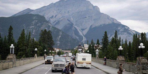 Pedestrians cross the street in Banff, Alta., in Banff National Park on July 21, 2017.