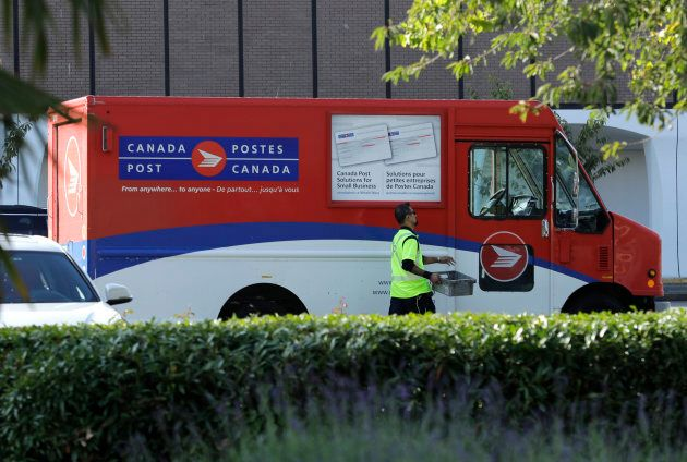 A Canada Post worker walks to his truck in Richmond, British