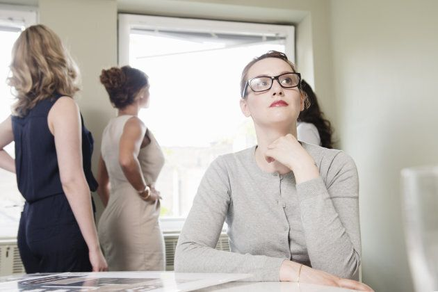 Young businesswoman gazing whilst colleagues look out of