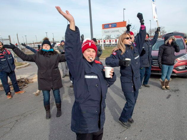 Striking Canada Post workers cheer honking motorists as they walk the picket line in front of the Saint-Laurent...