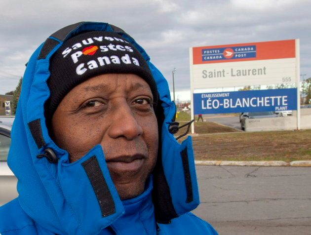 Striking Canada Post workers walk the picket line in front of the Saint-Laurent sorting facility in Montreal...