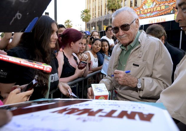 """Comic book legend Stan Lee signs autographs to fans at the premiere of Marvel's """"Ant-Man"""" on June 29, 2015."""
