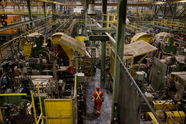 An employee walks between machines that process logs at the West Fraser Timber Co. sawmill in Quesnel,...