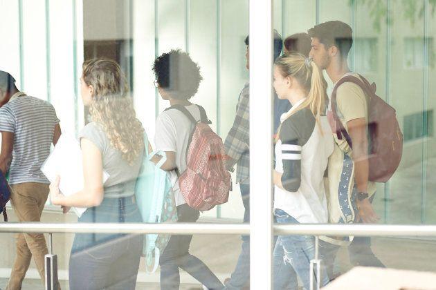 Students walking in school corridor, viewed through window
