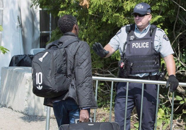 An asylum seeker is questioned by an RCMP officer near Champlain, N.Y. on Aug. 21,