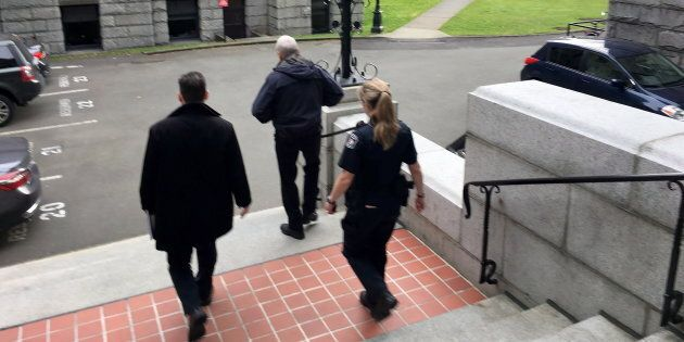 B.C. legislature sergeant-at-arms Gary Lenz is escorted out of the legislature by security in Victoria,...