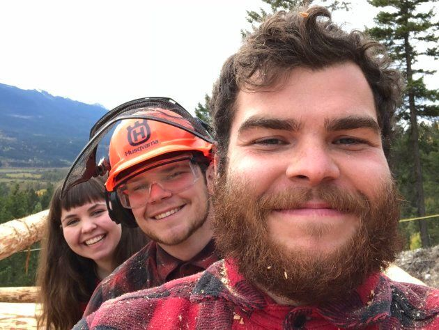 Siblings Andrew (r), Cameron, and Emily (l) pose for a photo on the build site of their family cabin.
