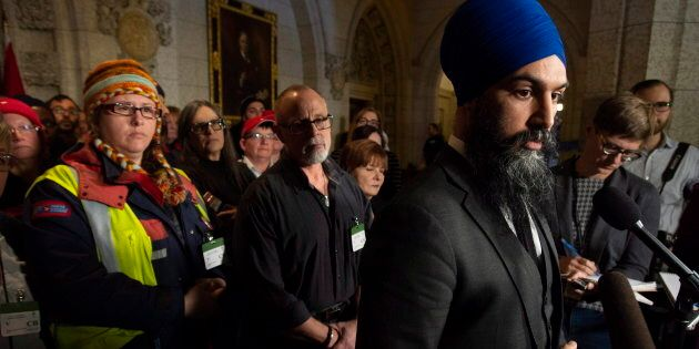 Surrounded by members of Canada Post NDP leader Jagmeet Singh listens to a question from the media about back to work legislation on Nov. 23, 2018 in Ottawa.