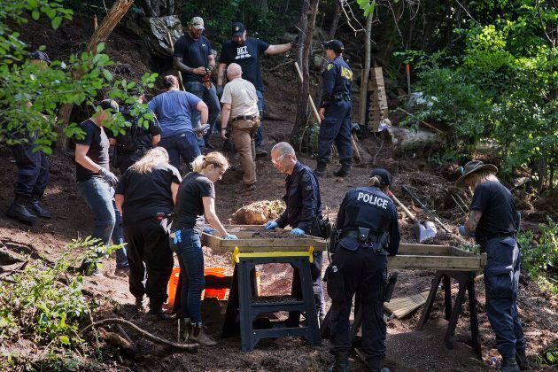 Investigators sift through compost looking for human remains in the back area of 53 Mallory Crescent...
