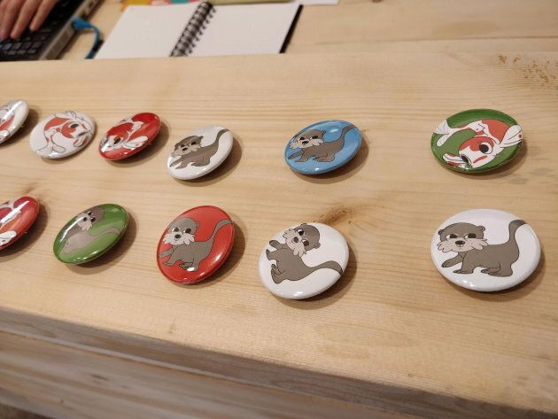 Buttons featuring cartoon koi and otters for sale by non-profit group Chinatown